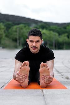 公園でヨガの練習をしている若いラテンゲイ。手で足を持ち、カメラを見ています。シートフォワードベンドヨガポーズまたはパスキモッタナサナ