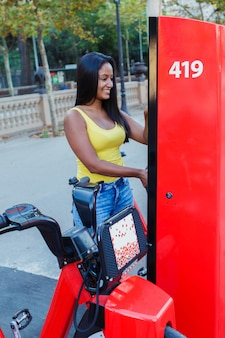 거리에 있는 자전거 가판대에서 자전거를 빌리는 젊은 라틴 소녀