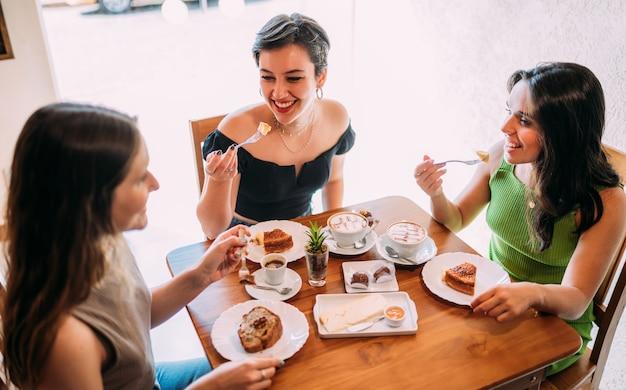 Молодые латинские девушки сидят в кафе, пьют кофе с пирожными и слушают забавную историю жизни