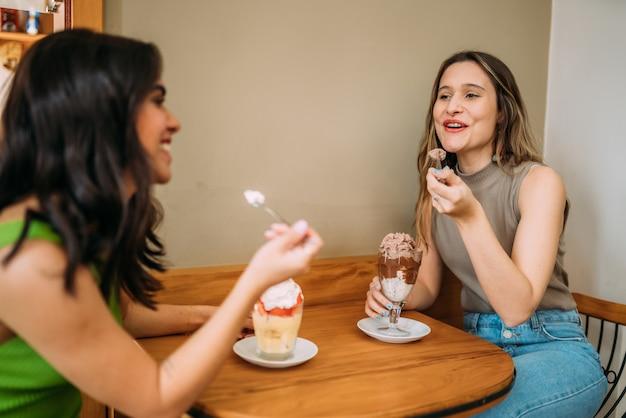 Молодые латинские девушки сидят в кафе и слушают забавную историю жизни своего друга