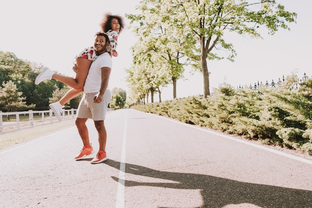 Young latin guy carries girlfriend on a hands in wood.