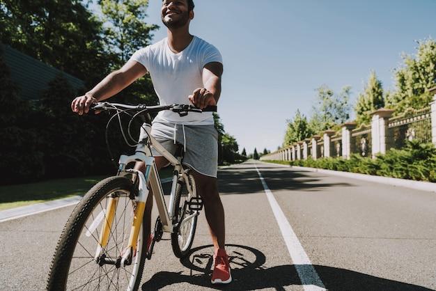 Молодой латинский парень едет на велосипеде. пустая дорога.