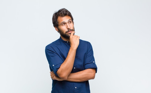 Молодой латинский красивый мужчина чувствует себя задумчивым, задается вопросом или воображает идеи, мечтает и смотрит вверх, чтобы скопировать пространство
