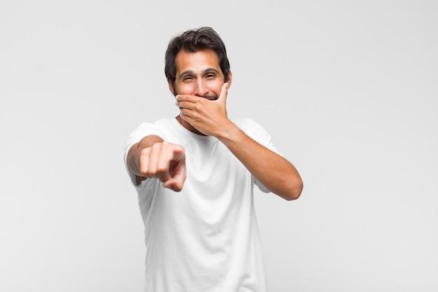 若いラテン系のハンサムな男があなたを笑い、正面を指して、あなたをからかったり、あざけったりします