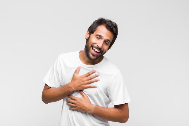 Молодой латинский красивый мужчина громко смеется над какой-то веселой шуткой, чувствует себя счастливым и веселым, веселится