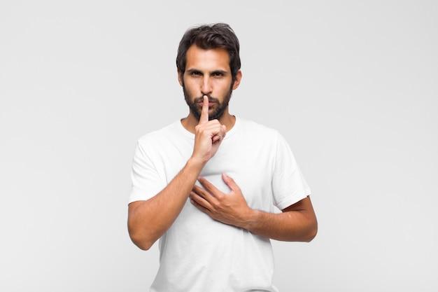 真面目そうに見える若いラテン系のハンサムな男は、秘密を守って、沈黙または静かを要求する唇に指を押して交差します