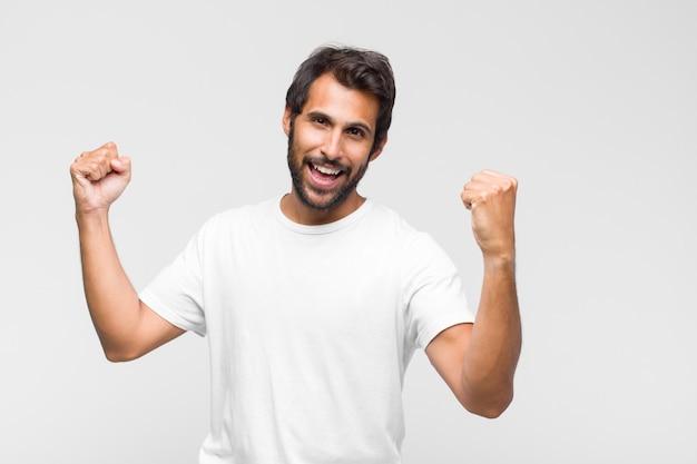 Молодой латинский красивый мужчина улыбается и чувствует себя расслабленным, довольным и беззаботным, позитивно смеется и пугает