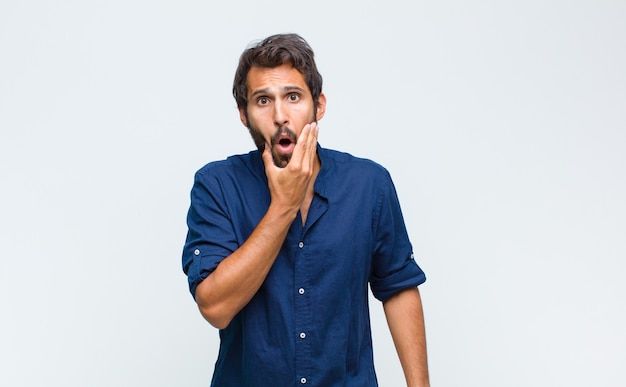 Young latin handsome man with mouth and eyes wide open and hand on chin, feeling unpleasantly shocked