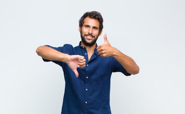 親指を上に、親指を下にした若いラテンハンサムな男