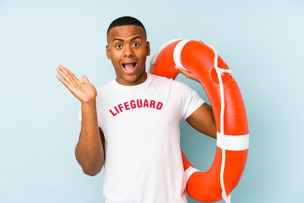 Young latin life guard on blue surprised and shocked.