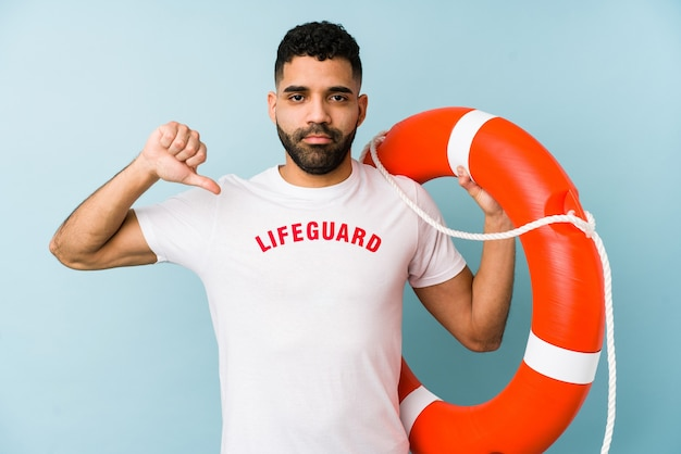 Young latin lifeguard man isolated showing a dislike gesture, thumbs down. disagreement concept.