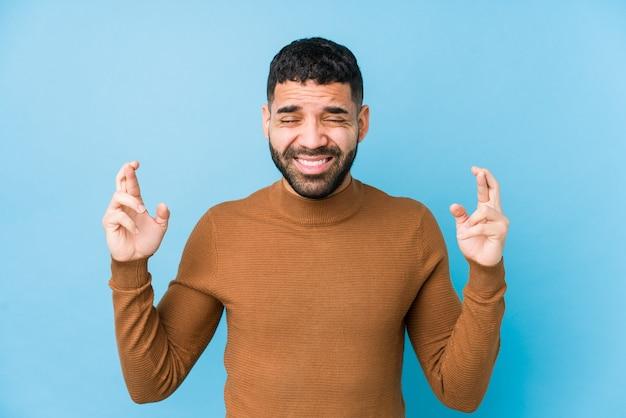 파란색 배경에 젊은 라틴 남자는 행운을 갖는 교차 손가락을 격리