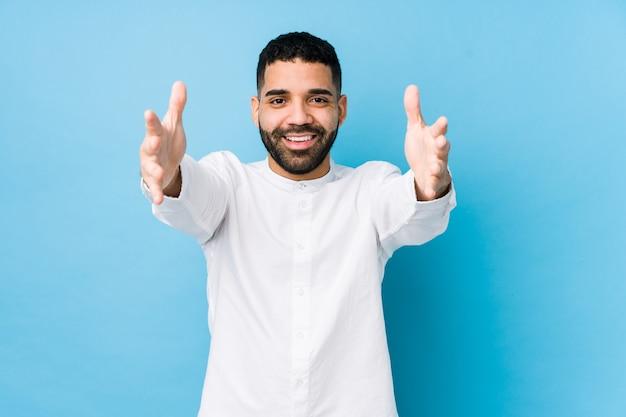 고립 된 파란색 벽에 젊은 라틴 남자는 포옹을주는 자신감을 느낀다