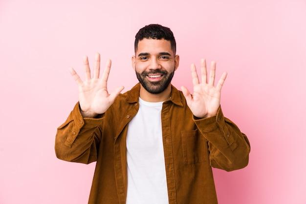 Молодой латинский человек на розовом фоне изолировал, показывая номер десять руками.