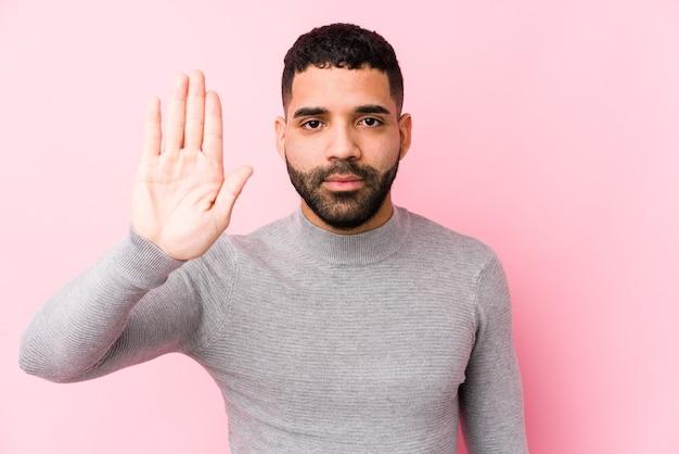 ピンクの背景の若いラテン男は一時停止の標識を示す差し出された手で立っているあなたを防ぎます。