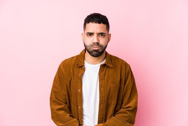 Молодой латинский мужчина против розового изолированного ударов щеками, имеет усталое выражение. концепция выражения лица.