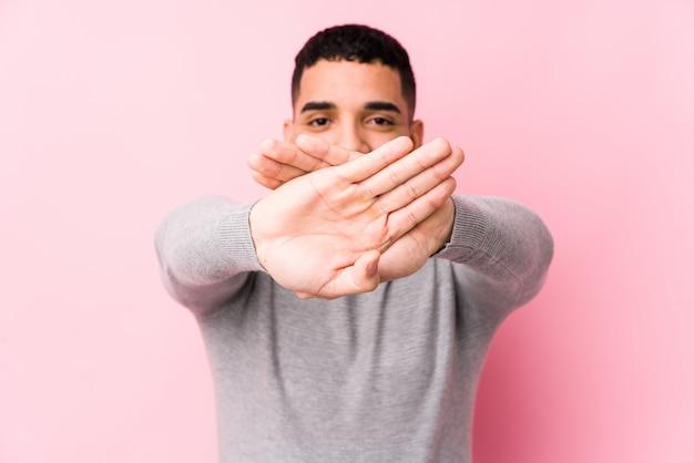 Молодой латинский человек против розовой стены изолировал делать жест отказа