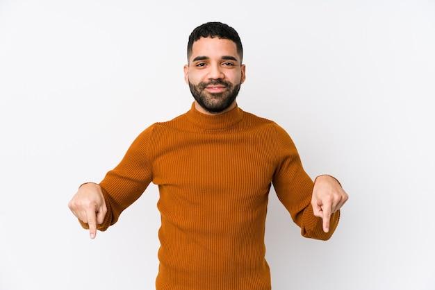 Молодой латинский человек на белом фоне изолированные указывает пальцами вниз, положительное чувство.