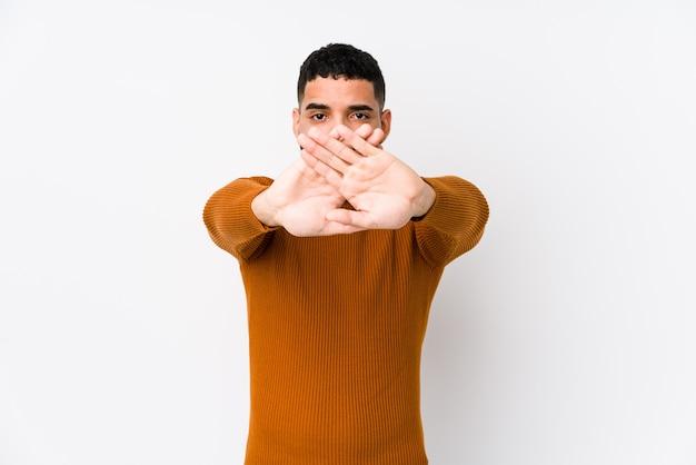 拒否のジェスチャーをしている白い壁に対して若いラテン男