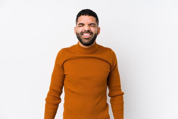 Молодой латинский мужчина на фоне белой стены смеется и закрывает глаза, чувствует себя расслабленным и счастливым.