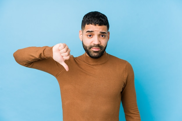Young latin man against a blue  wall isolated showing a dislike gesture, thumbs down. disagreement concept.