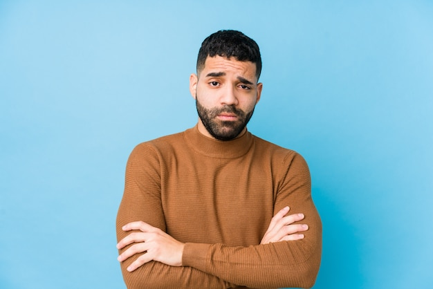 Young latin man against a blue  wall isolated unhappy with sarcastic expression.