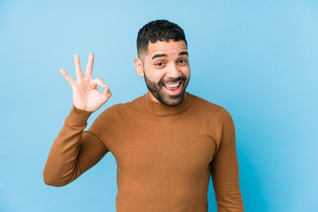 Young latin man against a blue  wall isolated winks an eye and holds an okay gesture with hand.