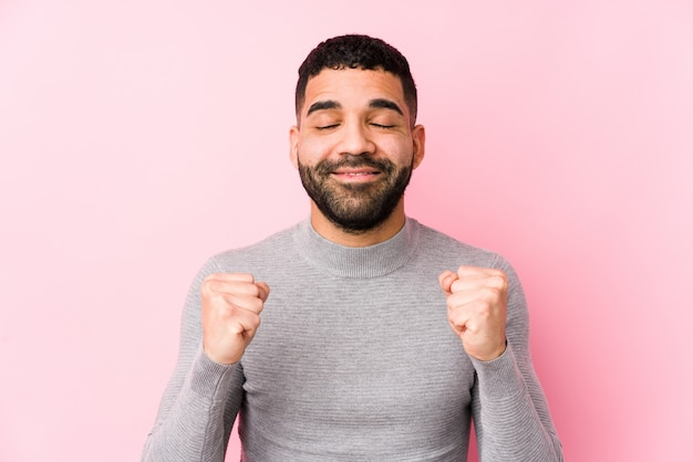 Young latin man against a pink background isolated raising fist, feeling happy and successful. victory concept.