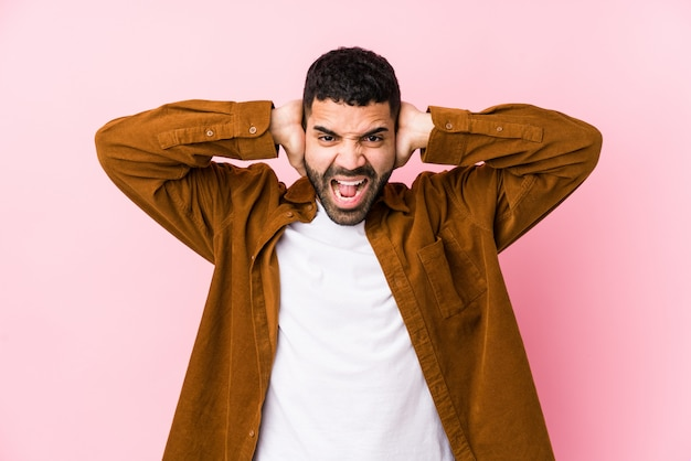 Young latin man against a pink wall isolated covering ears with hands trying not to hear too loud sound.