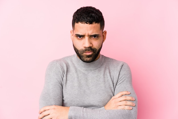 Young latin man against a pink wall isolated frowning face in displeasure, keeps arms folded.