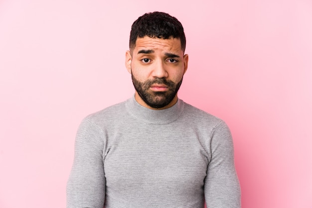 Young latin man against a pink wall unhappy looking with sarcastic expression.