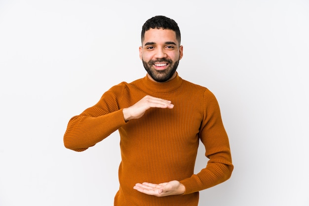 Young latin man against a white wall isolated holding something with both hands, product presentation.