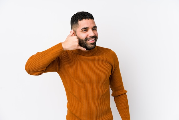 Young latin man against a white wall isolated showing a mobile phone call gesture with fingers.