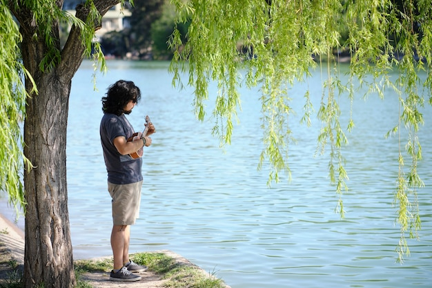 Young latin man alone with sunglasses, plays the ukulele at the shore of a lake.