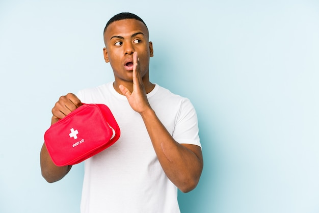 Young latin man doing first aid isolated is saying a secret hot braking news and looking aside