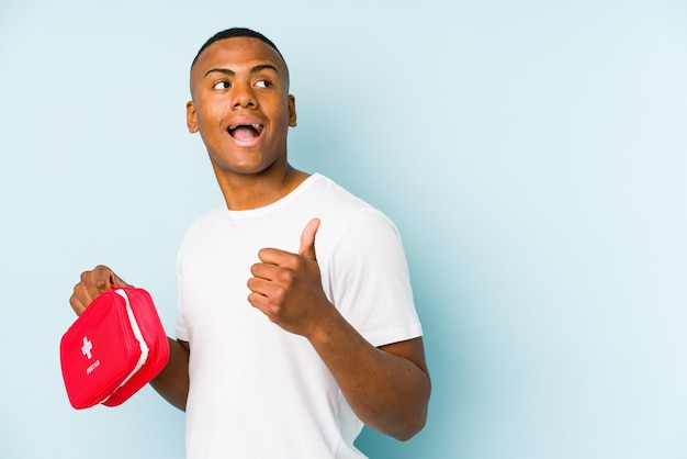 Молодой латинский человек делает изолированные точки первой помощи большим пальцем, смеясь и беззаботно.