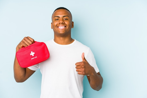 Young latin man doing first aid isolated smiling and raising thumb up