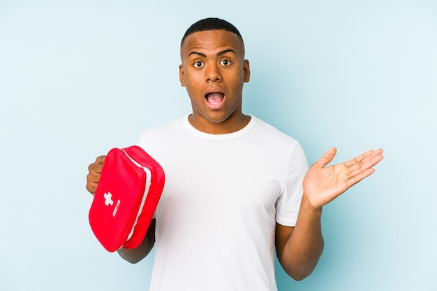 Young latin man doing first aid isolated surprised and shocked.