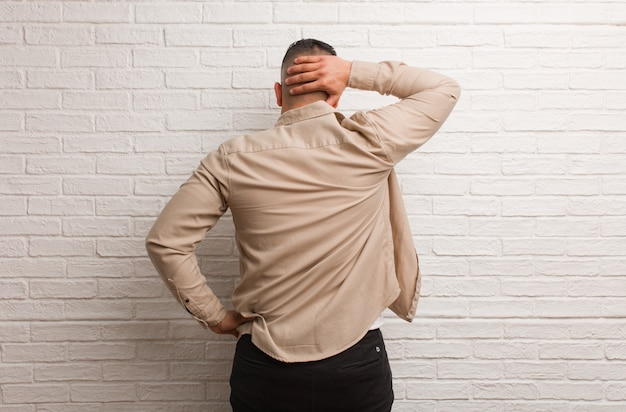 Young latin man from behind thinking about something