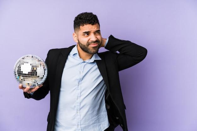 Молодой латинский мужчина держит партийный мяч в изоляции молодой латинский мужчина держит вафлю в изоляции, касаясь затылка, думает и делает выбор. <mixto>