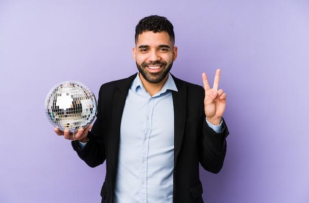 パーティーボールを保持している若いラテン男指で番号2を示す分離されたワッフルを保持している若いラテン男。