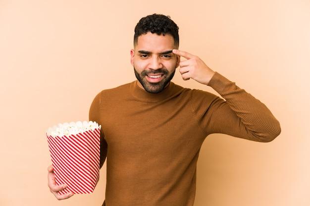 人差し指で失望のジェスチャーを示す分離されたポップコーンを保持している若いラテン男。