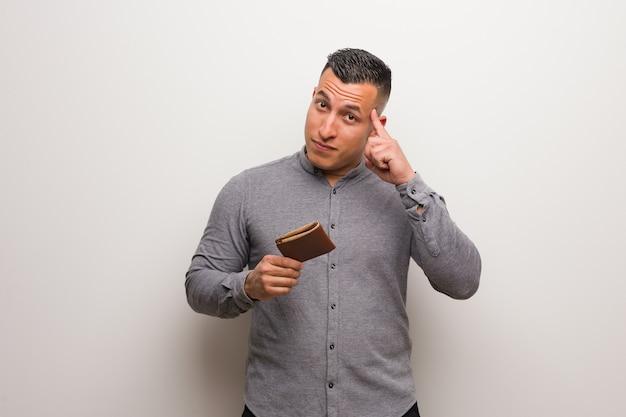 アイデアについて考えて財布を保持している若いラテン男