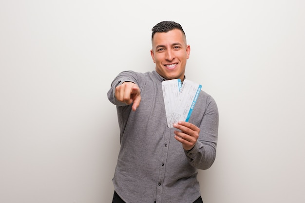 Young latin man holding an air tickets cheerful and smiling pointing to front