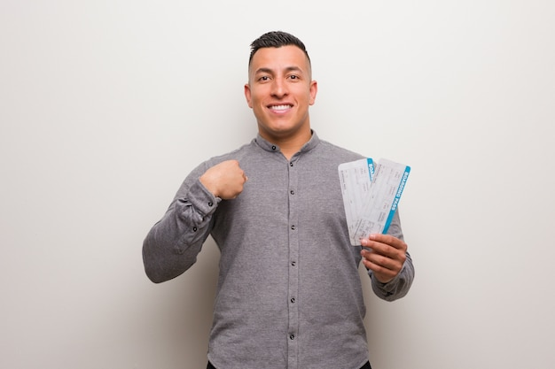 Young latin man holding an air tickets surprised, feels successful and prosperous