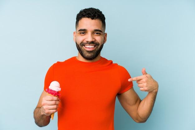 Молодой латинский мужчина держит мороженое изолированного человека, указывая рукой на пространство для копии рубашки, гордый и уверенный