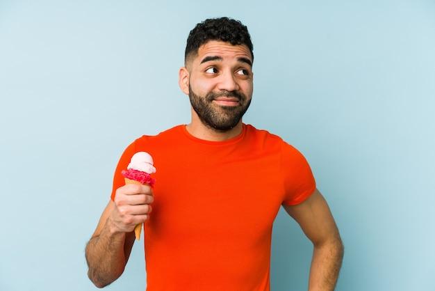 Молодой латинский мужчина держит мороженое