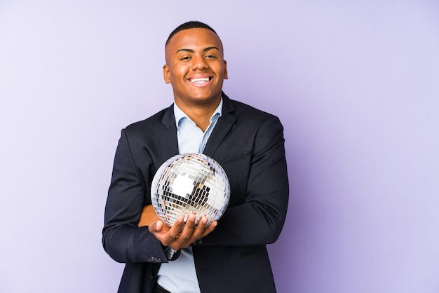 Young latin man holding a ball party isolated laughing and having fun.