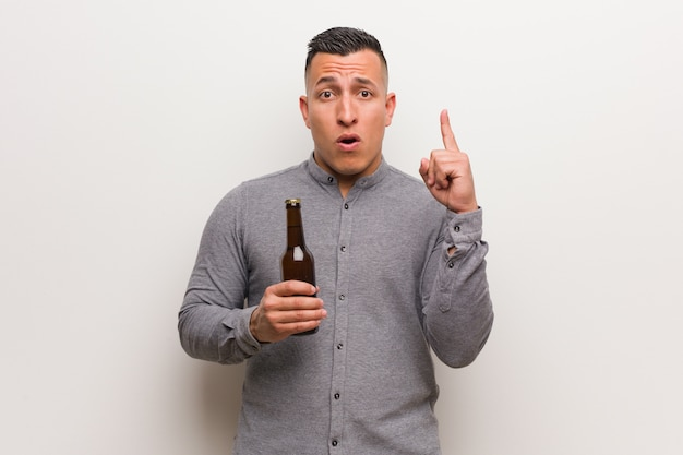 Young latin man holding a beer having a great idea