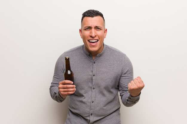 Young latin man holding a beer surprised and shocked
